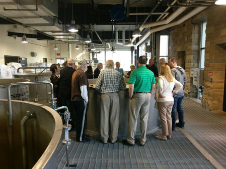 group of people gathered in a circle around a fermenter