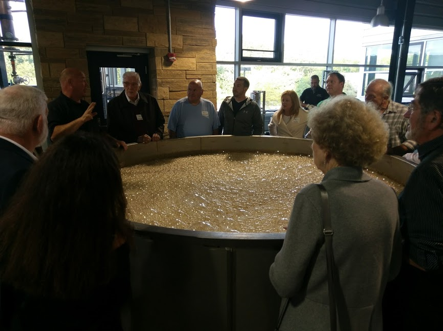 group of people standing around a fermenter watching a demostration