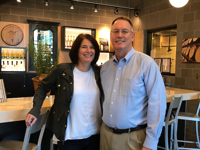 a man and woman in business casual standing together smiling in front of a bar at New Riff Distillery